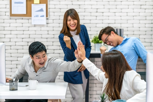 Group of asian business people celebrating and giving high five together with happiness