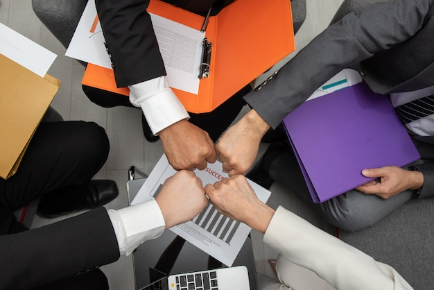Group of asian business people hands making fist bump gesture together in teamwork.