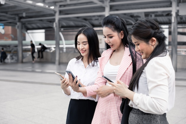 Group of asian business woman playing mobile with a smile at outdoor in city. concept of teamwork asian woman. thai women office worker group.