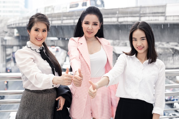 Group of asian business woman thumbs up with a smile at outdoor in city. concept of teamwork asian woman. thai women office worker group.