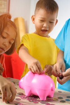 Group of asian children are helping putting coins into piggy bank on white background