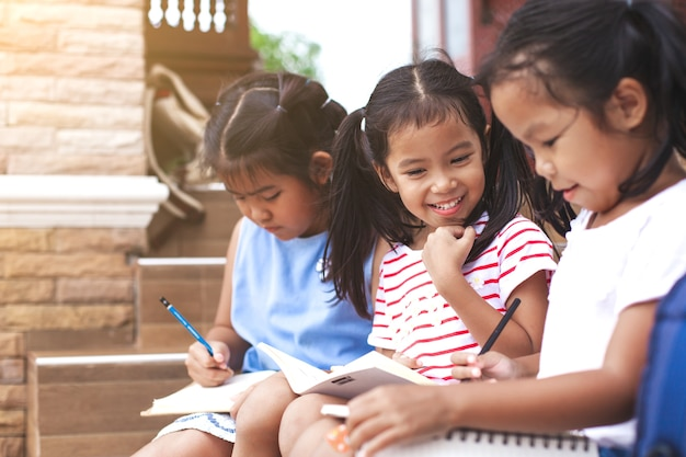 Group of asian children reading a book and writing a notebook together