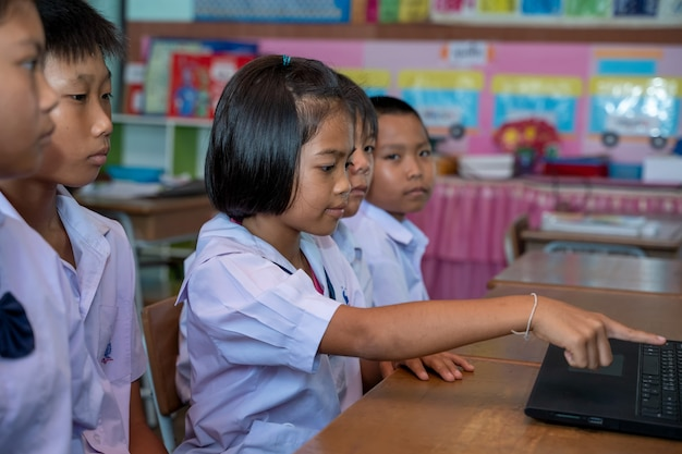 Group of asian elementary school students learning to use laptop together at classroom