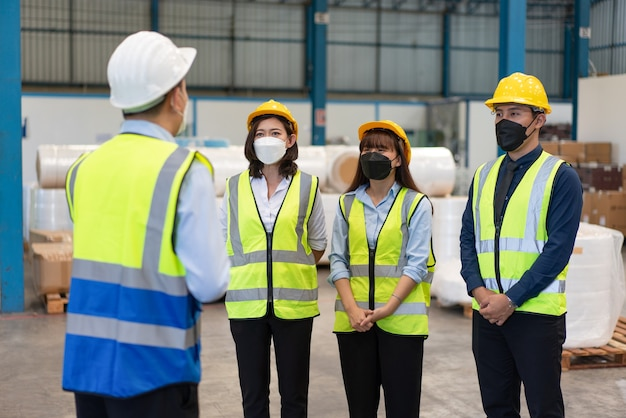 Group asian engineer wear mask protect with helmet safety standing meeting before to work in factory