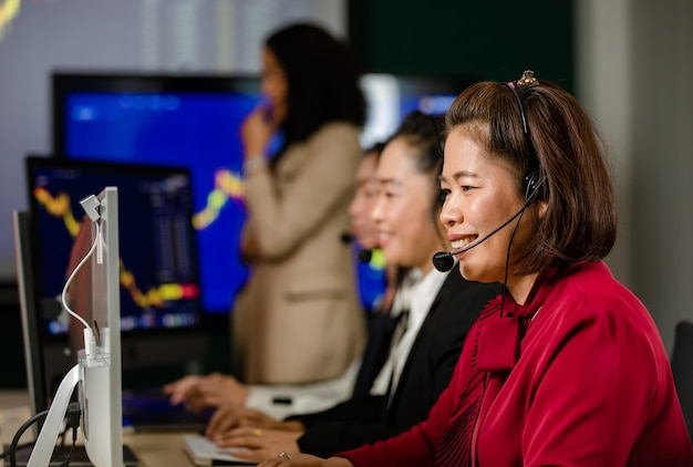 Group of asian female customer service operators wears microphone headsets sit smiling in front daily graph chart computer monitor screen talking and trading buy sell stock market online with client.
