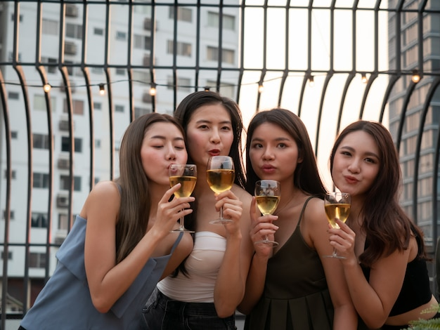 Group of asian friend cheering and drinking at terrace party. young people toasting glass with wine at rooftop restaurant