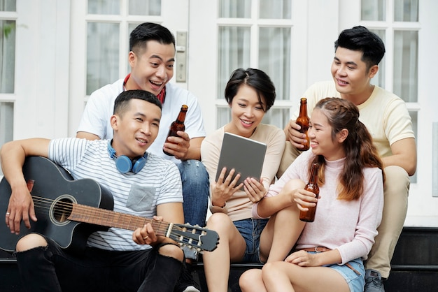 Group of asian friends drinking beer and singing songs while playing guitar during a party