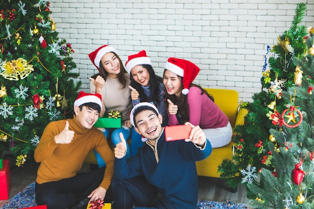 Group of asian friends taking selfie with friend together by smartphone at home during chrismas eve party or new year celebrate party. happy winter xmas and happy new year party concept