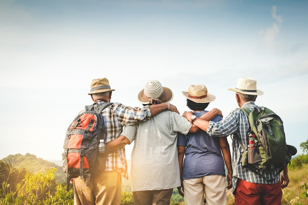 Group of asian seniors hiking and standing on high mountains enjoying nature. senior community concepts