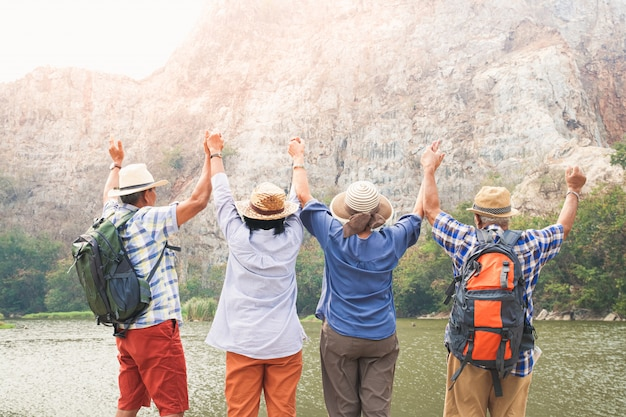 A group of asian seniors hiking and standing on high mountains enjoying nature. senior community concepts