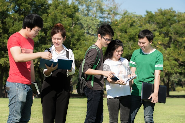Group of asian students dressed casual standing on park outdoors
