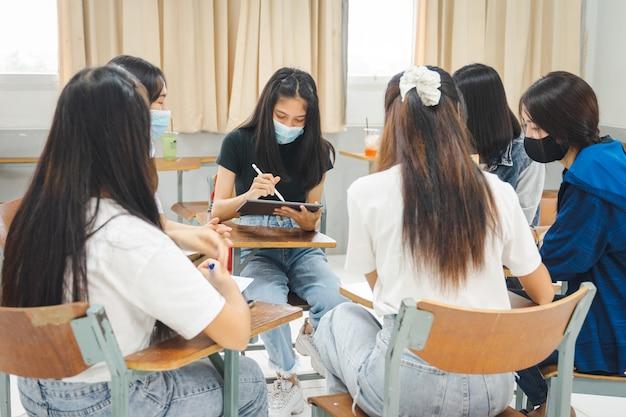 그룹 아시아 대학생들은 보호용 안면 마스크를 쓰고 교실에서 프로젝트에 대해 토론합니다.
