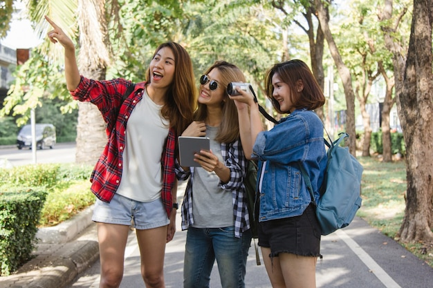 Group of asian women using camera to make photo while traveling at park in urban city in bangkok