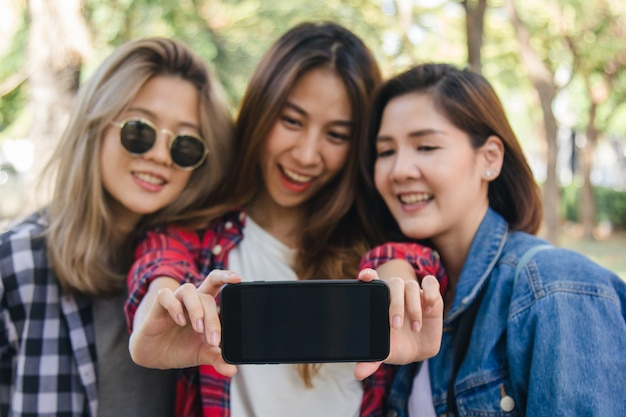 Group of asian women using smartphone taking selfie while traveling at park in urban city in bangkok