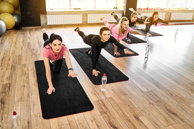 Group of athletic women doing pushups on the floor and stretching exercises in the gym