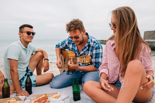 Group of attractive friends having a picnic, playing guitar on the beach, while eating pizza