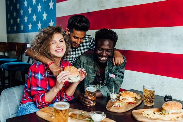 Gruppo di amici attraenti che si abbracciano, mangiano hamburger, parlano e sorridono mentre trascorrono del tempo insieme in gastropub.