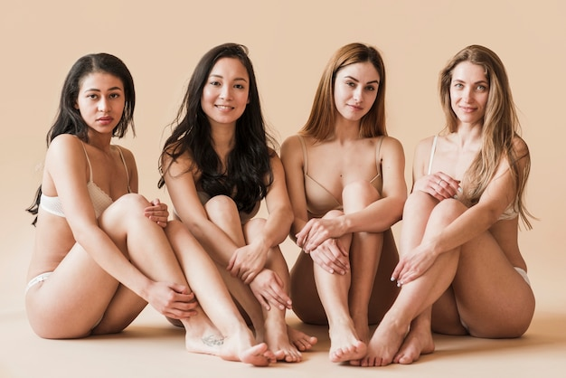 Group of attractive young women in underwear sitting in studio