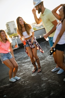 Group of beautiful carefree friends dancing have fun in summer