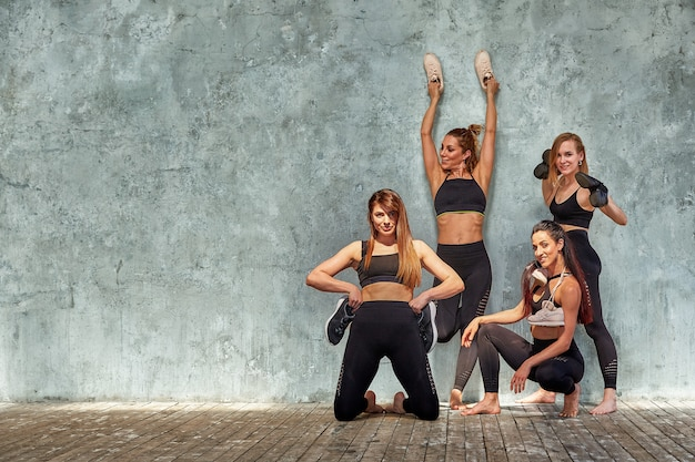 Group of beautiful fitness girls posing with sports accessories against a gray wall