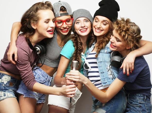 Group of beautiful stylish hipster girls singing karaoke