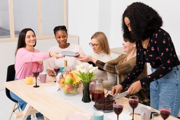 Group of beautiful women getting cake