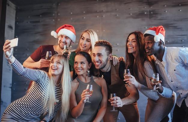 新年会でselfieをしている美しい若い人々、親友の女の子と男の子が一緒に楽しんで、感情的なライフスタイルの人々のポーズをグループ化します。帽子サンタとシャンパングラスを手に