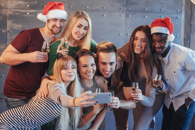 Group beautiful young people doing selfie in the new year party, best friends girls and boys together having fun, posing emotional lifestyle people. hats santas and champagne glasses in their hands