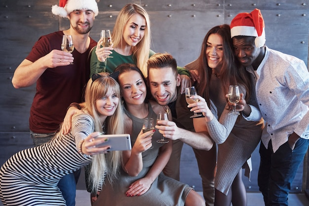 Group beautiful young people doing selfie in the new year party, best friends girls and boys together having fun, posing lifestyle people concept. hats santas and champagne glasses in their hands