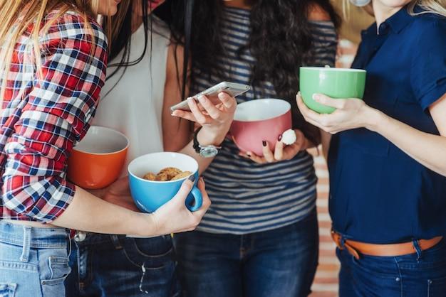 会話を楽しんだり、コーヒーを飲んだり、親友の女の子が一緒に楽しんで、感情的なライフスタイルをポーズ美しい若い人々をグループ化します。
