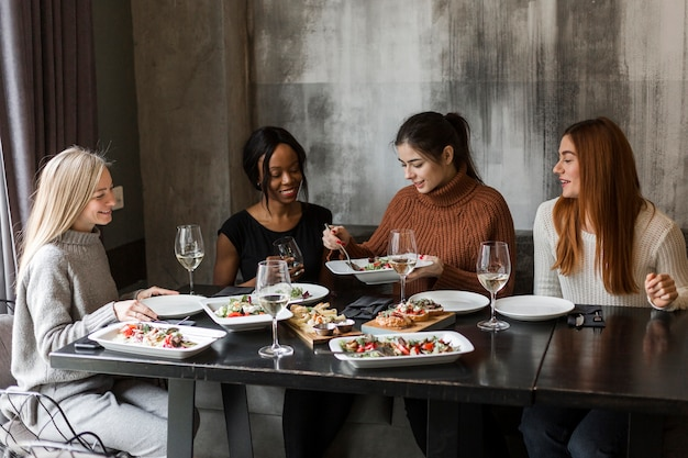 Group of beautiful young women enjoying dinner together