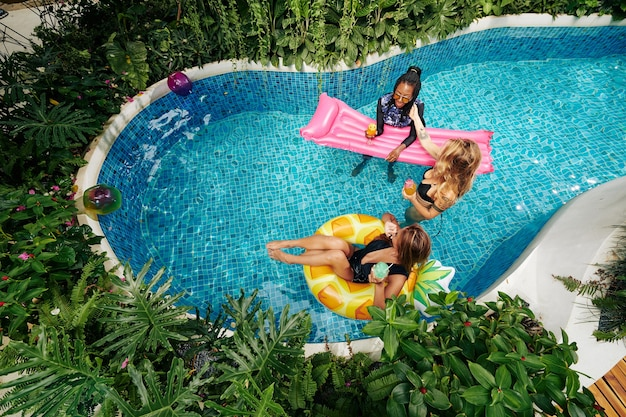 Group of beautiful young women relaxing in swimming pool, drinking cocktails and chatting