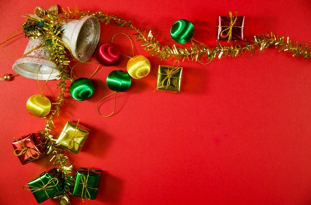 Group of bell, ball and gift in christmas on red background on top view