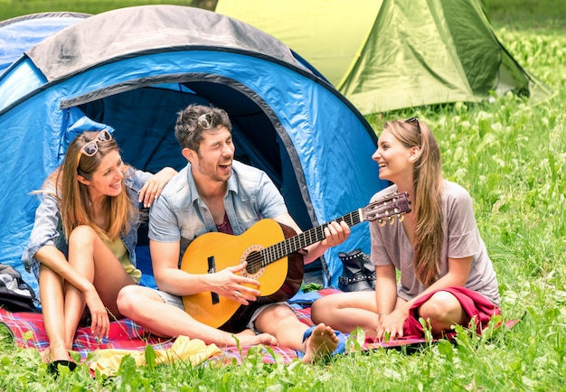 Group of best friends singing and having fun camping together