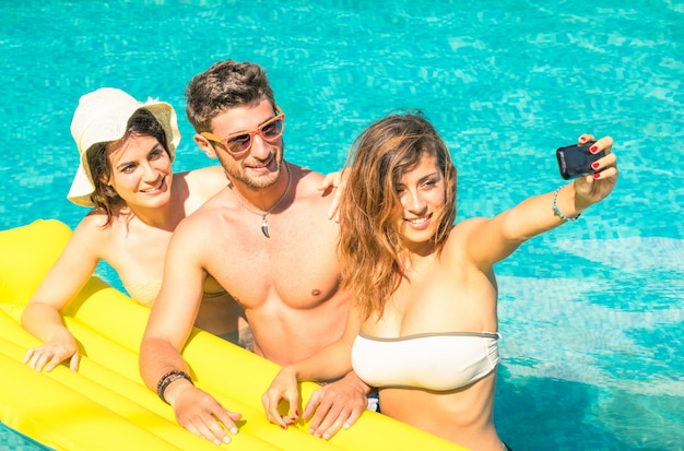 Group of best friends taking selfie at swimming pool on yellow airbed