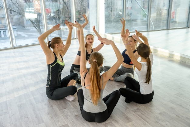 Group of beutiful women practicing yoga in gym
