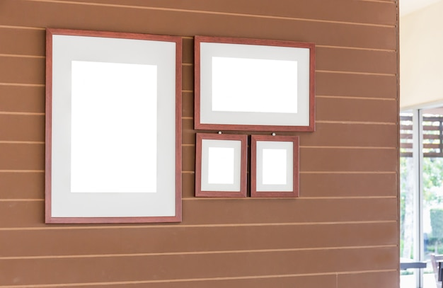 Group of blank photo frames on the wall for your design