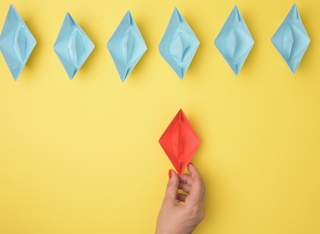 A group of blue paper boats follows a red boat in front of a yellow background. the concept of a strong and charismatic leader in a team, manipulating the masses, top view