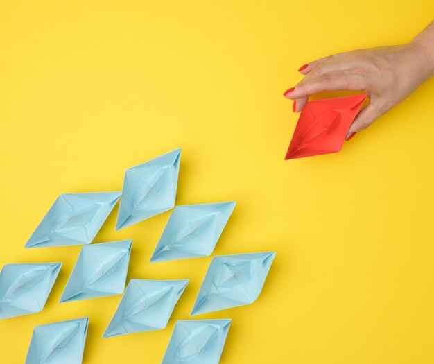 A group of blue paper boats follows a red boat in front of a yellow background