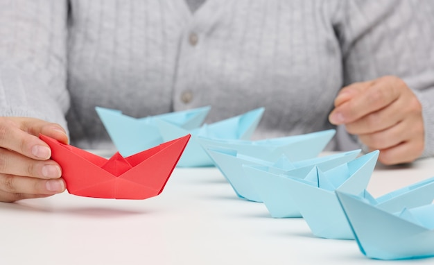 Group of blue paper boats follows a res boat in front of a white table. the concept of a strong and charismatic leader in a team, manipulating the masses
