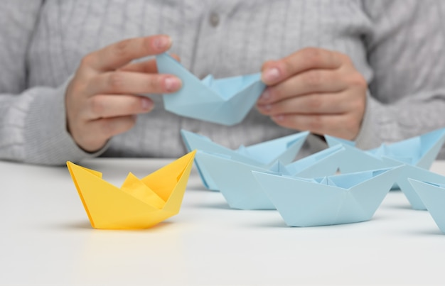 Group of blue paper boats follows a yellow  boat in front of a white background. the concept of a strong and charismatic leader in a team, manipulating the masses