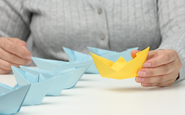 Group of blue paper boats follows a yellow boat in front of a white table. the concept of a strong and charismatic leader in a team, manipulating the masses