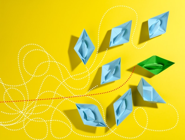 Group of blue paper boats and one green with paths on a yellow background concept of a strong lead