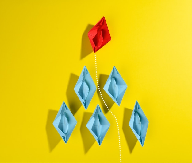 Group of blue paper boats and one red led on a yellow background. strong leader concept, growth of unique and talented employees, top view