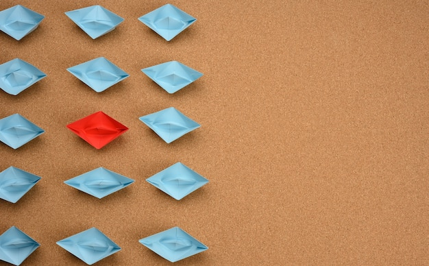 Group of blue paper boats and one red in the middle on a brown surface. the concept of a unique and extraordinary personality in a team. talented employee, be yourself