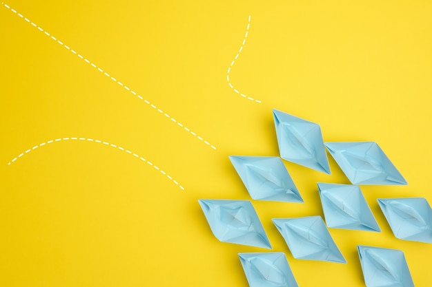 Group of blue paper boats with different paths on yellow background, path choice concept. teamwork