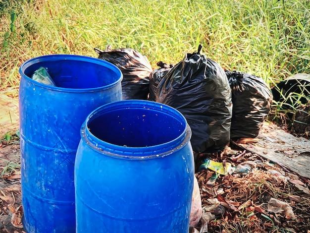 Group of blue plastic trash bins and tied black garbage bags