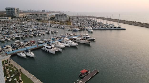 Group of boats are moored together at a small marina in the herzliya marina.