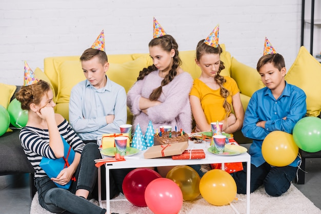 Group of bored friends sitting in the birthday party