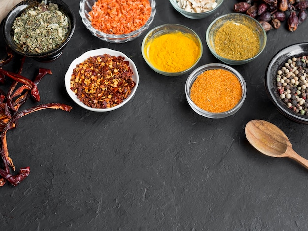Group of bowls full of spices on black background